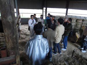 牛舎内で参加者に説明する小松さんの写真